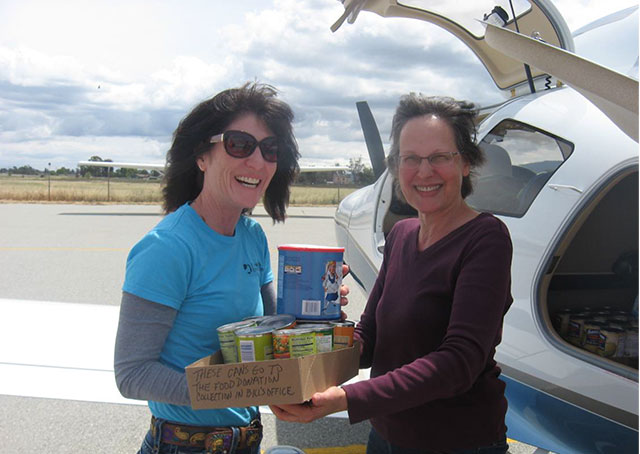SCAPA pilot and longtime board member Bette Gardner hands the first food donation to Vicky Martin of the St Joseph's Family Center Food Pantry program. Photo courtesy of SCAPA/Paul Marshall.