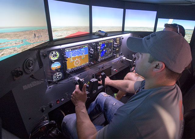 Nik Oekerman (left) gets some instruction from Jeff Wolf in a Redbird simulator.