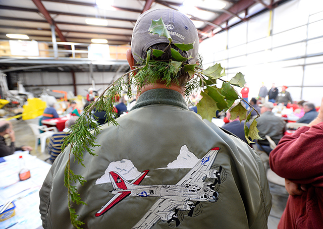 Flight instructor Daniel Wroe wears a sprig of greenery on his cap during the Tangier Island Holly Run breakfast at Chesapeake Sport Pilot in Stevensville, Maryland.