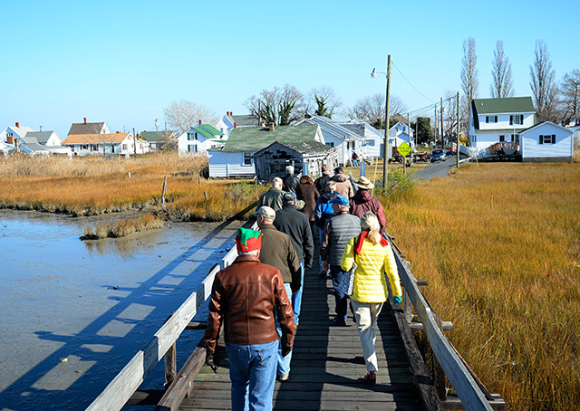 Aviators file across a narrow wooden bridge during the annual Tangier Island Holly Run to the small Virginia island in the middle of the Chesapeake Bay Dec. 5. Photos by David Tulis.