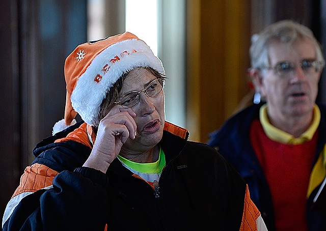 "Carol Moore wipes a tear from her eye as she joins Tangier Island residents and visiting pilots singing ""Silent Night"" during a Swain Memorial United Methodist Church service."