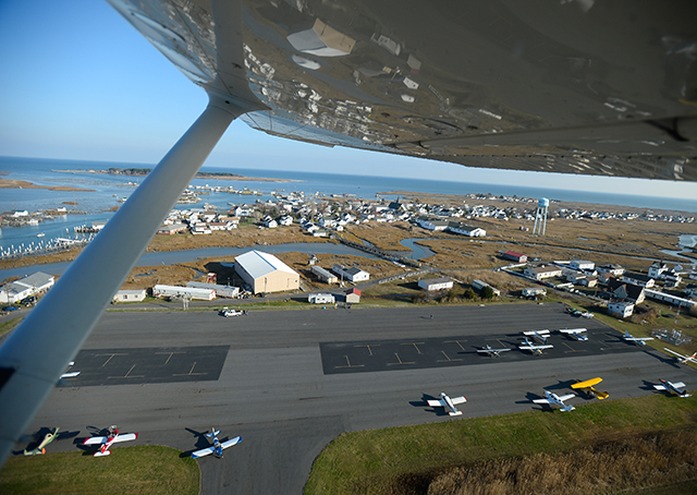Tangier Island Airport unfolds under the wing of a departing Cessna 172.