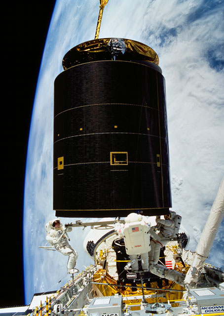 Heavy lifting may be required: on May 13, 1992, following the successful capture of the Intelsat VI satellite, three astronauts continue moving the 4.5 ton communications satellite into the space shuttle Endeavour's cargo bay. NASA photo.