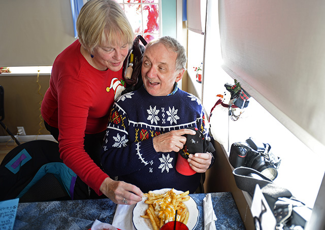 "Congressional Flying Club member Ruth Hornseth steals a crab-covered fry from husband Geoff during the annual Tangier Island ""Holly Run"" flight Dec. 5. The Hornseths said the club provides a social scene attracting pilots and non-pilots alike. Photo by David Tulis."