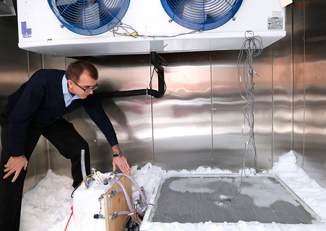 Halil Ceylan checks a test slab that uses heated pavement technology to melt snow and ice. One of the goals of the research project is to help smaller airports clear runways during winter storms. Photo by Christopher Gannon, courtesy of Iowa State University.