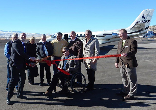 The new Hot Springs County Airport near Thermopolis, Wyoming, opened to the public Nov. 7, ushering in margins of safety and night operations at the gateway to Yellowstone Country. Hot Springs County Commissioner Chair Brad Basse cuts the airport's ribbon and is joined by Former County Commissioner Mike Baker, U.S. Representative Cynthia Lummis (R-Wyo.), County Commissioner Thomas Ryan, U.S. Senator John Barrasso (R-Wyo.), County Commissioner John Lumley, Gov. Matt Mead, Thermopolis native and former Gov. Dave Freudenthal, and GDA Engineers Project Manager Jeremy Gilb. Photo by Warren Hendrickson.