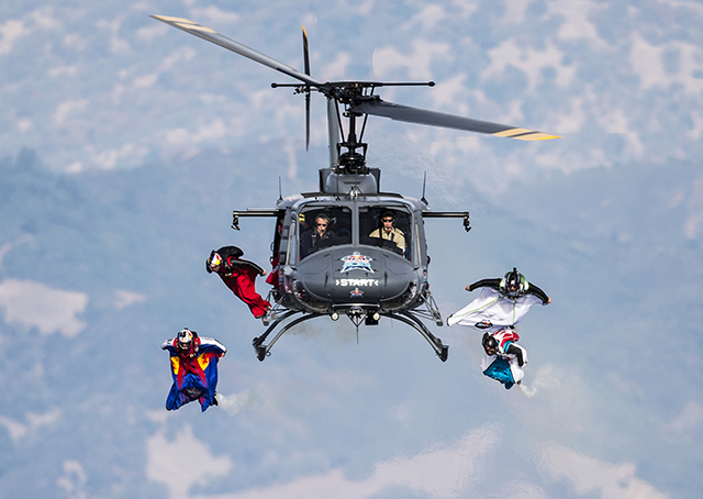 Competitors begin their wingsuit flights from a helicopter during the Red Bull Aces, a wingsuit four-cross race, over Cloverdale, California. Defending champion Andy Farrington of the United States was victorious in the race that pits four competitors flying by aerial gates suspended by helicopters. Joerg Mitter/Red Bull Content Pool.