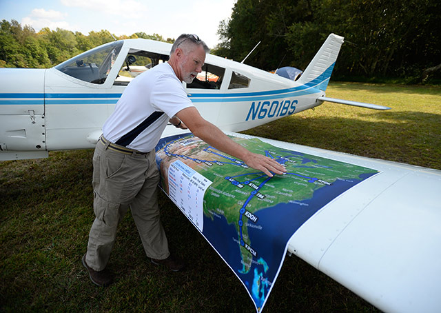 Ed Loxterkamp of Cincinnati, who flew his Piper Arrow to every 2015 AOPA Fly-In, plus EAA AirVenture and the Sun 'n Fun Fly-In, spreads out a map documenting his adventures. Photo by David Tulis.