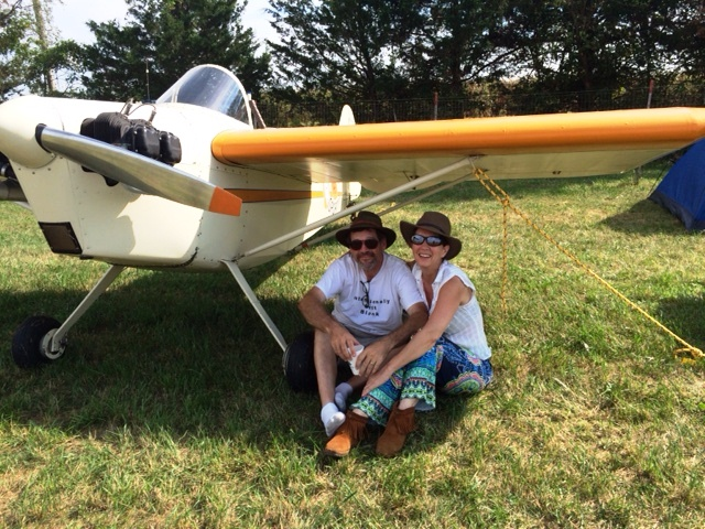 Rob and Laura Bach sit under the wing of their Bentzen Sport at the Antique Airplane Association fly-in.